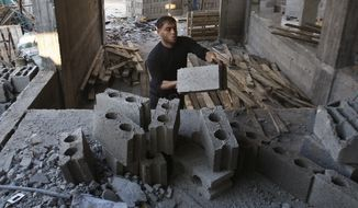 Palestinian workers rebuild a house in Gaza City on Dec. 31, 2012. (Associated Press)
