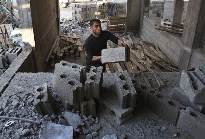 Palestinian workers rebuild a house in Gaza City on Dec. 31,