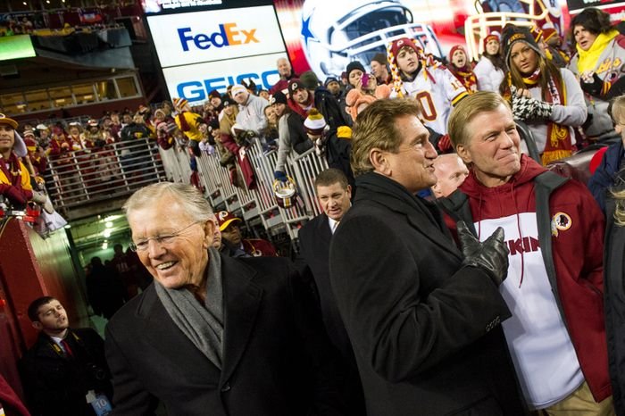 Former Washington Redskins head coach Joe Gibbs, left, former Redskins quarterback Joe Theismann, second from right, and Virginia Gov. Bob McDonnell, right, talk together on the field before the Washington Redskins' game against the Dallas Cowboys at FedEx Field, Landover, Md., Sunday, Dec. 30, 2012. (Andrew Harnik/The Washington Times)