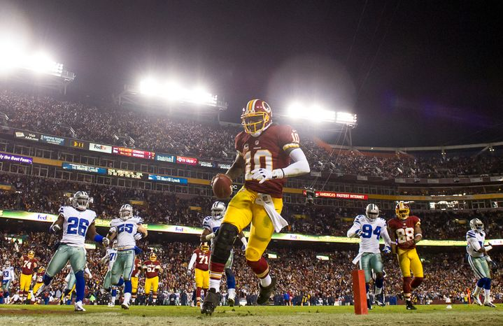 Washington Redskins quarterback Robert Griffin III (10) keeps it himself and scores on a 10-yard run in the third quarter at FedEx Field, Landover, Md., Sunday, Dec. 30, 2012. (Andrew Harnik/The Washington Times)