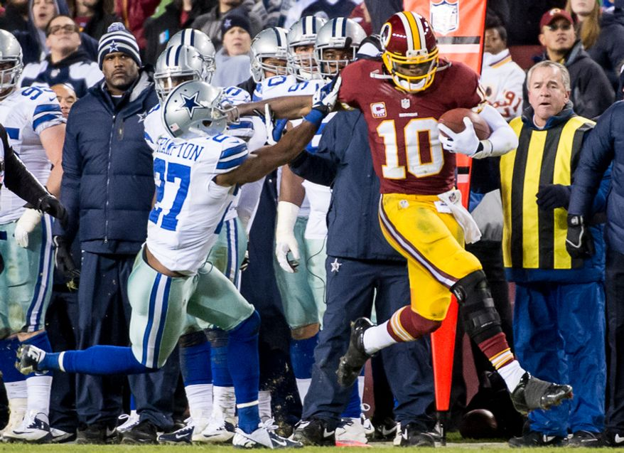 Washington Redskins quarterback Robert Griffin III (10) stiff arms Dallas Cowboys strong safety Eric Frampton (27) as he goes out of bounds after a 17-yard run at FedEx Field, Landover, Md., Sunday, Dec. 30, 2012. (Andrew Harnik/The Washington Times)