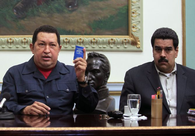 ** FILE ** Venezuelan President Hugo Chavez (left) holds up a copy of the Venezuelan Constitution as Vice President Nicolas Maduro looks on during a televised speech at the Miraflores presidential palace in Caracas, Venezuela, on Saturday, Dec. 8, 2012. (AP Photo/Miraflores Press Office, Marcelo Garcia)