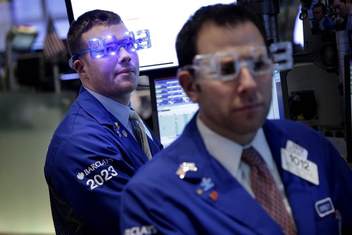 """Traders wear """"2013"""" glasses as they work on the floor at the New York Stock Exchange in New York, Monday, Dec. 31, 2012. The stock market struggled for direction Monday morning after five days of losses, with the """"fiscal cliff"""" just hours away and lawmakers yet to reach a solution. (AP Photo/Seth Wenig)"""
