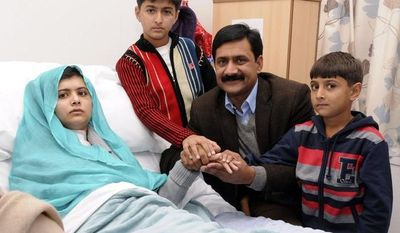 Malala Yousufzai sits in her hospital bed as her father, Ziauddin (second from right), accompanied by her two younger brothers, Atal (right) and Khushal, sit by, in this undated photo issued by Queen Elizabeth Hospital in Birmingham, England, on Friday, Oct. 26, 2012. The 15-year-old Pakistani girl, who was shot in the head Oct. 9 in Pakistan by the Taliban, is recovering at the Birmingham hospital, where she was flown for treatment and protection from Taliban threats. (Associated Press/Queen Elizabeth Hospital, Birmingham)