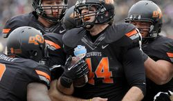 Oklahoma State tight end Jeremy Seaton (44) celebrates with teammates after a first-half touchdown against Purdue during the Heart of Dallas Bowl NCAA college football game, Tuesday, Jan. 1, 2013, in Dallas. (AP Photo/Matt Strasen)