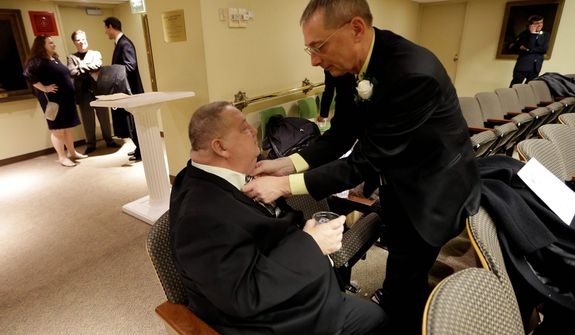 William Countryman (right) adjusts partner Roy Neal's tie before participating in a marriage ceremony at City Hall in Baltimore on Tuesday, Jan. 1, 2013. Same-sex couples in Maryland are now legally permitted to marry under a new law that went into effect after midnight on Tuesday. Maryland is the first state south of the Mason-Dixon Line to approve same-sex marriage. (AP Photo/Patrick Semansky)