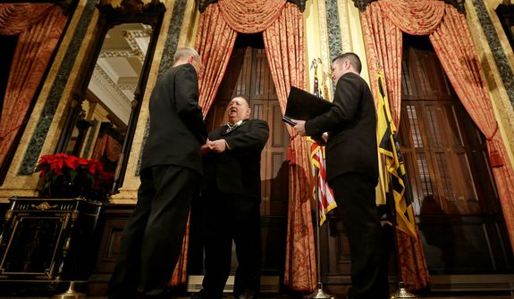 William Countryman (left) and Roy Neal exchange vows as officiant Jason Caton looks on during a marriage ceremony at City Hall in Baltimore on Tuesday, Jan. 1, 2013. Same-sex couples in Maryland are now legally permitted to marry under a new law that went into effect after midnight on Tuesday. Maryland is the first state south of the Mason-Dixon Line to approve same-sex marriage. (AP Photo/Patrick Semansky)