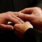 Thomas Rabe, right, places a wedding ring on Robert Coffman's finger during a marriage ceremony at City Hall in Baltimore, Tuesday, Jan. 1, 2013. (AP Photo/Patrick Semansky) ** FILE **