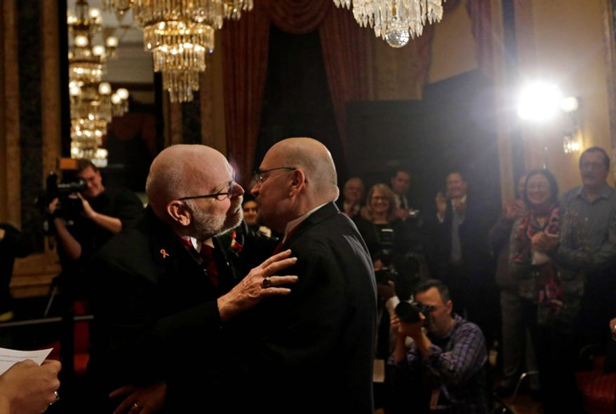 James Scales (left) and William Tasker kiss during their marriage ceremony at City Hall in Baltimore on Tuesday, Jan. 1, 2013. Same-sex couples in Maryland are now legally permitted to marry under a new law that went into effect after midnight on Tuesday. Maryland is the first state south of the Mason-Dixon Line to approve same-sex marriage. (AP Photo/Patrick Semansky)