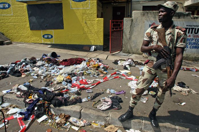 An Ivory Coast soldier stands next to the belongings of people involved in a deadly stampede in Abidjan, Ivory Coast, early on Tuesday, Jan. 1, 2013. At least 61 people were killed following a New Year's fireworks display, and the death toll is expected to rise, officials said. (AP Photo/Emanuel Ekra)