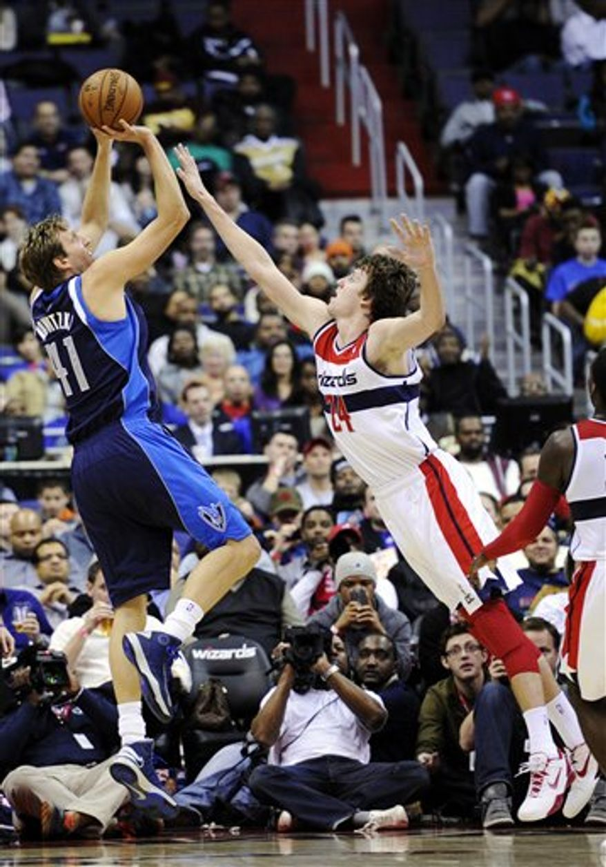 Dallas Mavericks forward Dirk Nowitzki (41) shoots against Washington Wizards forward Jan Vesely (24) during the second half of an NBA game, Tuesday, Jan. 1, 2013, in Washington. Dallas won 103-94. (AP Photo/Nick Wass)