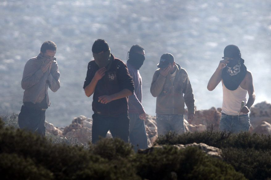Palestinians protesters react to tear gas shot by Israeli soldiers during clashes near the West Bank village of Qusra, near Nablus, on Tuesday, Jan. 1, 2013. (AP Photo/Nasser Ishtayeh)