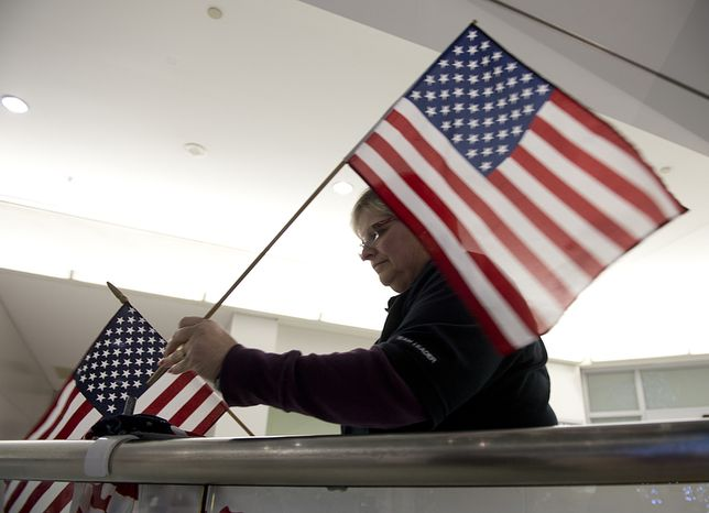 ** FILE ** Jan Feldman with Operation Welcome Home Maryland puts up American flags at the international arrivals area of BWI Thurgood Marshall Airport on Friday, Dec. 28, 2012, in preparation of welcoming a charter flight of military personnel back home. The welcome organization has greeted more than 800 flights and 180,000 troops since its inception in 2007. (Barbara L. Salisbury/The Washington Times)