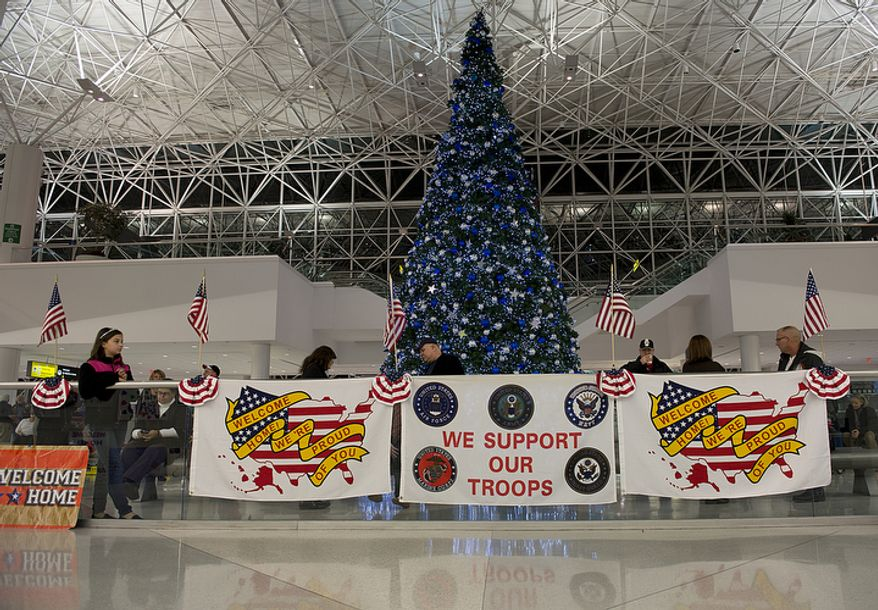 Friends and family members, including Caroline Brenninkmeyer [cq], left, 12, of Falls Church, Va., waiting for her dad, await the arrival of the Delta charter flight bringing home members of the military at BWI Thurgood Marshall Airport on Friday, Dec. 28, 2012. The flags and signs were put in place by Operation Welcome Home Maryland, which greets every incoming flight and wants to make troops' first encounter back on U.S. soil after deployment as positive as possible. (Barbara L. Salisbury/The Washington Times)