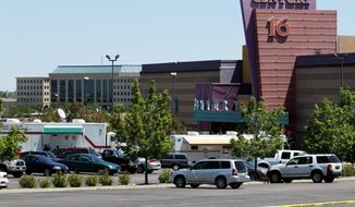 ** FILE ** Emergency vehicles remain at the Century 16 movie theater in Aurora, Colo., on July 21, 2012, after 12 people were fatally shot in the theater. (Associated Press)