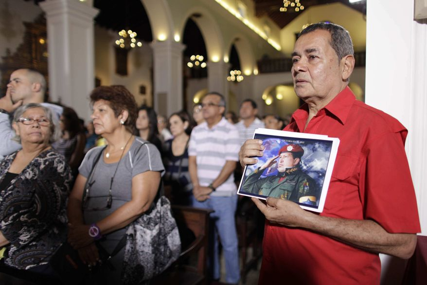 People, one of them holding an image of Venezuela's President Hugo Chavez, gather to pray for him at a church in Caracas, Venezuela, Monday, Dec. 31, 2012. (AP Photo/Ariana Cubillos)