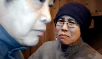 **FILE** In this image made Dec. 28, 2012, from a video and provided by Hu Jia via AP Video, Liu Xia (right), wife of 2010 Nobel Peace Prize winner Liu Xiaobo, reacts to an unexpected visit by a group of activists at her home in Beijing. (Associated Press/Hu Jia via AP Video)