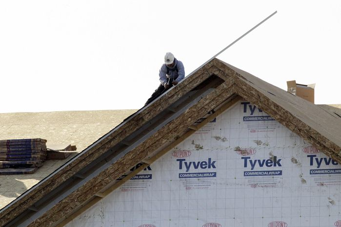 ** FILE ** In this Nov. 28, 2012, photo, a worker constructs a home i