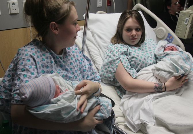 Twin sisters Aimee (left) and Ashlee Nelson hold their newborn sons Donavyn Bratten (left) and Aiden Lee Alan Dilts at Summa Akron City Hospital on Dec. 31, 2012, in Akron, Ohio. The mothers, 19, gave birth about two hours apart. (Associated Press/Akron Beacon Journal, Michael Chritton)