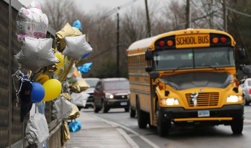 ** FILE ** In this Dec. 18, 2012, file photo, a school bus rolls toward a memorial in Newtown, Conn., for victims of the Sandy Hook Elementary School shooting. Nearly three weeks after the shooting rampage, classes are starting Thursday, Jan. 3, 2013, for the Sandy Hook students at a repurposed school in the neighboring town of Monroe, where the students' desks have been taken along with backpacks and other belongings that were left behind in the chaos following the shooting on Dec. 14. (AP Photo/Charles Krupa, File)