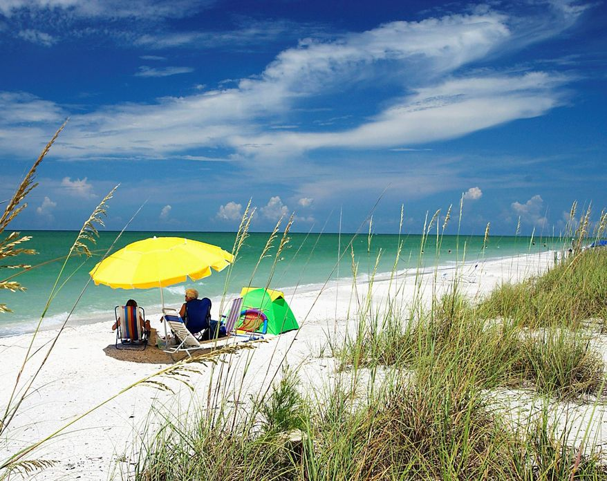 ** FILE ** Beach-goers find some shade on Sanibel Island in Florida. (Sanibel & Captiva Chamber of Commerce photographs)