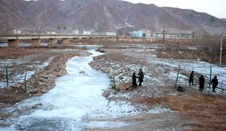 Chinese paramilitary policemen build a fence Dec. 8 across from North Korea, seen in the background from the Chinese border town of Tumen. In recent months, North Korean strongman Kim Jong Un has intensified a border crackdown that has sought to seal the once-porous 880-mile frontier with China, smugglers and analysts alike say. (Associated Press)