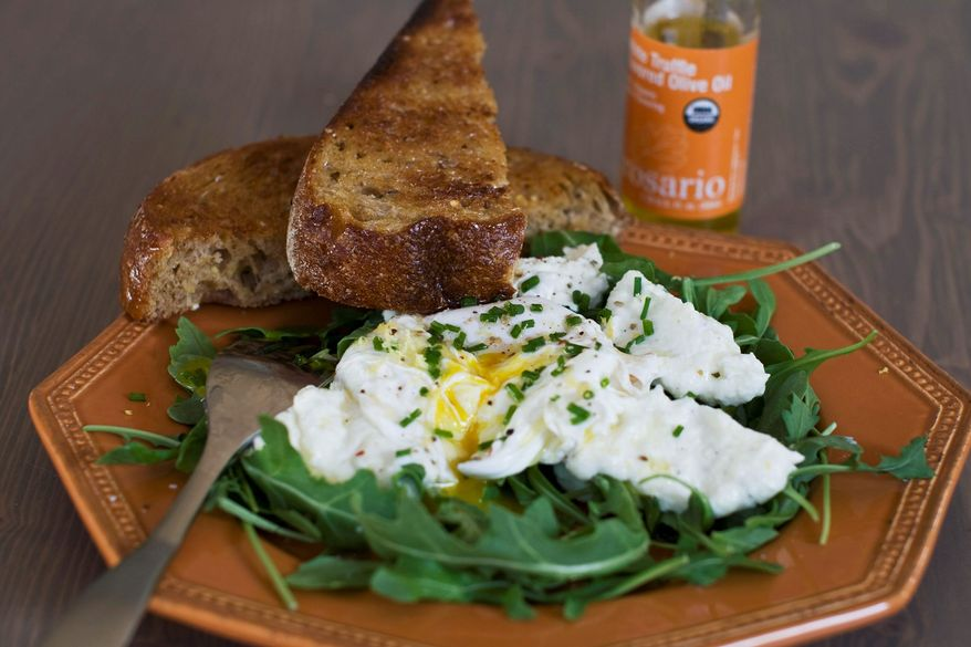 Poached eggs over ricotta cheese on arugula turn a salad into a meal that can be enjoyed for breakfast, lunch or dinner. (Associated Press)