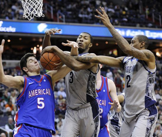 American guard Marko Vasic (5) battles for the ball against Georgetown forward Mikael Hopkins (3) and Greg Whittington (2) during the first half of an NCAA college basketball game, Saturday, Dec. 22, 2012, in Washington. (AP Photo/Nick Wass)