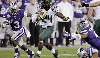 Oregon running back Kenjon Barner (24) escapes the reach of Kansas State linebacker Arthur Brown (4) and Allen Chapman (3) during the second half of the Fiesta Bowl college football game, Thursday, Jan. 3, 2013, in Glendale, Ariz. (AP Photo/Matt York)