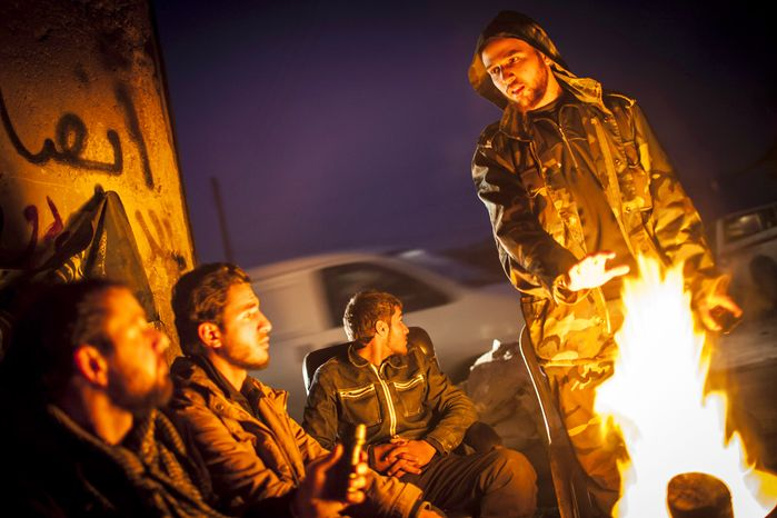 Syrian rebels gather around a fire as they plan patrols in the Saif al-Dawlah neighborhood of Aleppo, Syria, on Wednesday, Jan. 2, 2013. (AP Photo/Andoni Lubaki)