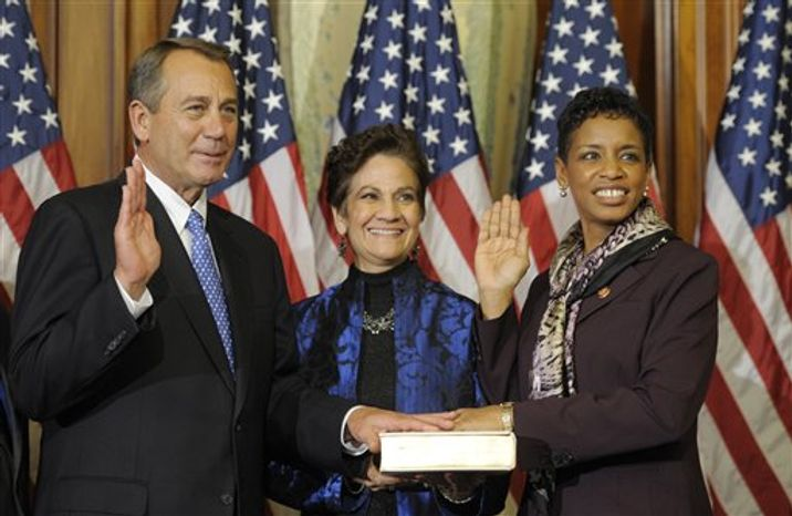 House Speaker John A. Boehner, Ohio Republican, performs a mock swearing-in ceremoney for Rep. Donna F. Edwards (right), Maryland Democrat, on Thursday, Jan. 3, 2013, on Capitol Hill in Washington as the 113th Congress began. (AP Pho