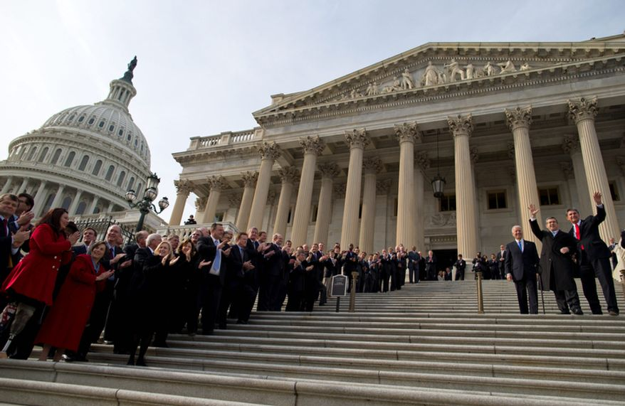 Members of Congress line the steps to the Senate door of the Capitol building on Capitol Hill in Washington, Thursday, Jan. 3, 2013, as Sen.  Mark Kirk, R-Ill., second from right, accompanied by Sen. Joe Manchin, D-W.Va., right, and Vice President Joe Biden, waves as he walks the steps to mark his return to Congress. Kirk said he often visualized climbing the 45 steps of the U.S. Capitol as a source of inspiration during his months of grueling physical therapy after suffering a major stroke last year.  (AP Photo/ Evan Vucci)