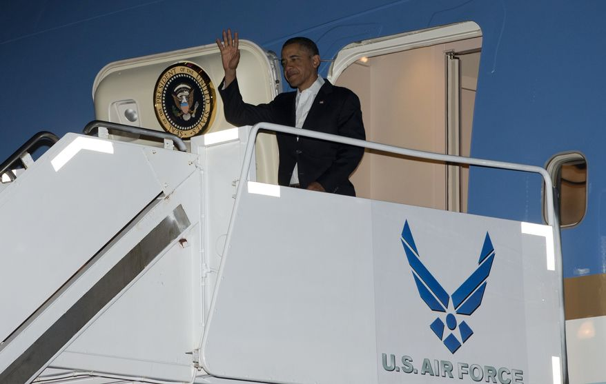 """President Obama waves as he deplanes from Air Force One upon his arrival at Joint Base Pearl Harbor-Hickam in Honolulu, Hawaii, on Wednesday, Jan. 2, 2013. The president is back in Hawaii for vacation after a tense, end-of-the-new-year standoff with Congress over the """"fiscal cliff."""" (AP Photo/Carolyn Kaster)"""