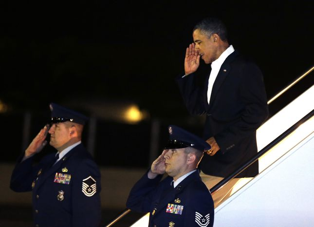 "President Obama salutes as he deplanes from Air Force One upon his arrival at Joint Base Pearl Harbor-Hickam in Honolulu on Wednesday, Jan. 2, 2013. The president is back in Hawaii for vacation after a tense, end-of-the-new-year standoff with Congress over the ""fiscal cliff."" (AP Photo/Gerald Herbert)"