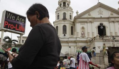 "A ""Pro-Life"" message flashes on an electric signboard outside the Roman Catholic Minor Basilica of the Black Nazarene in downtown Manila on Thursday, Jan. 3, 2013. (AP Photo/Aaron Favila)"