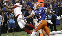 Louisville wide receiver DeVante Parker (9) catches a touchdown pass as Florida defensive back Loucheiz Purifoy (15) defends in the first half of the Sugar Bowl college football game Wednesday, Jan. 2, 2013, in New Orleans. (AP Photo/Dave Martin)