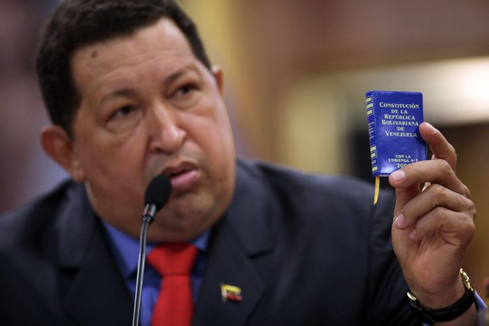 ** FILE ** Venezuelan President Hugo Chavez holds a miniature copy of his country's constitution during a news conference in Caracas, Venezuela, on Oct. 9, 2012. (AP Photo/Rodrigo Abd)