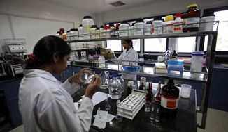 ** FILE ** In this March 13, 2012, file photo, Indian scientists work inside a laboratory of the Research and Development Centre of Natco Pharma Ltd. in Hyderabad, India. (AP Photo/Mahesh Kumar A., File)