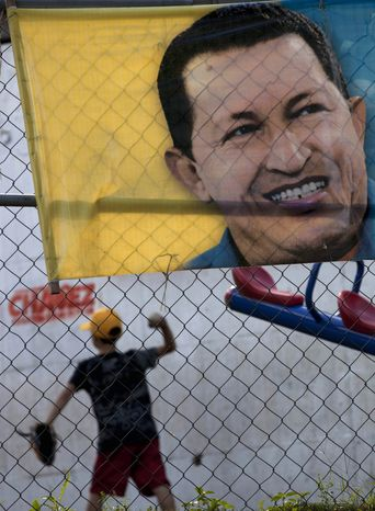 A boy plays behind a poster with an image depicting Venezuelan President Hugo Chavez in Caracas, Venezuela, on Jan. 3, 2013. The ailing president's health crisis has raised contentious questions ahe