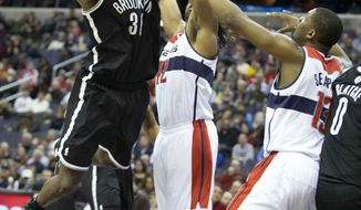 Brooklyn Nets' Reggie Evans (30) shoots against Washington Wizards defenders Nene (42) of Brazil and Kevin Seraphin (13) of France during the first half of an NBA basketball game in Washington, Friday, Jan. 4, 2013. (AP Photo/Manuel Balce Ceneta)