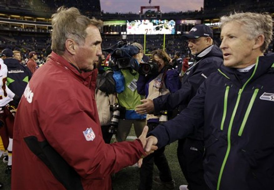 FILE - This Nov. 27, 2011 file photo shows Seattle Seahawks head coach Pete Carroll, right, greeting Washington Redskins head coach Mike Shanahan, after the Redskins won 23-17 in an NFL football game in Seattle. Once nearly co-workers, Carroll and Shanahan will meet on Sunday, Jan. 6, 2013 in the NFC playoffs when Seattle visits Washington. (AP Photo/Ted S. Warren, File)