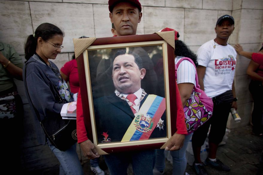 A supporter of Venezuela's President Hugo Chavez poses for a portrait as he holds a photograph of Chavez outside the National Assembly in Caracas, Venezuela, Saturday, Jan. 5, 2013. Just five days remain until Chavez's scheduled inauguration on Thursday, and government officials are suggesting the swearing-in could be delayed as the president fights a severe respiratory infection after cancer surgery in Cuba. (AP Photo/Ariana Cubillos)