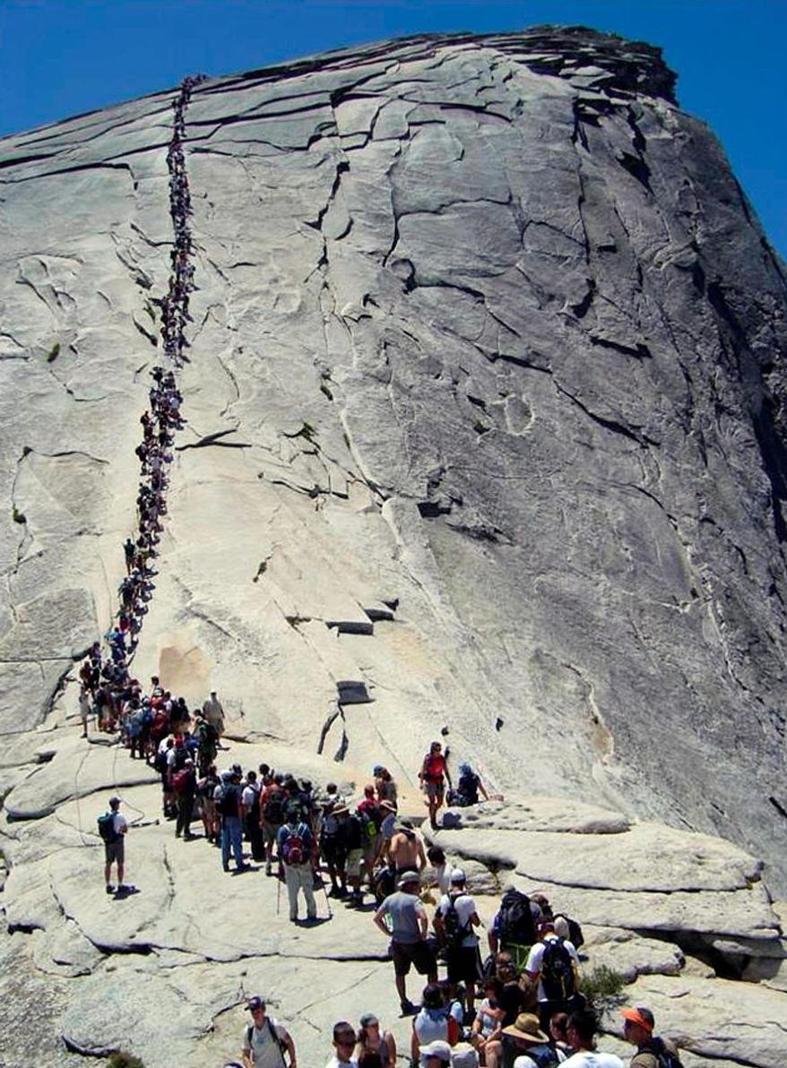 As many as 1,200 nature lovers a day have been climbing Half Dome at Yosemite National Park. A limit of 300 has been set to avoid traffic jams, especially when bad weather hits the dome that rises 5,000 feet above the valley. (National Park Service via Associated Press)