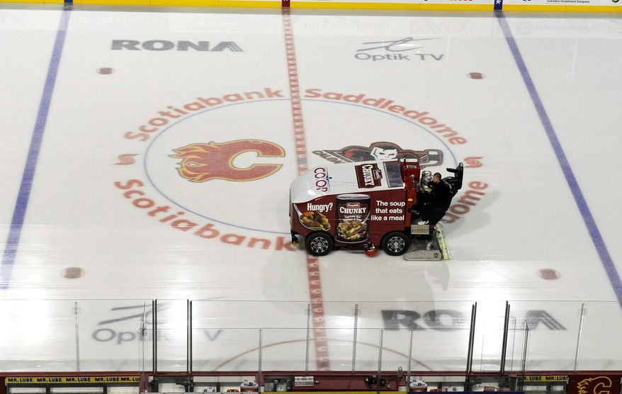 A Zamboni clears the ice at Scotiabank Saddledome, home of the Calgary Flames, on Sunday, the same day a tentative deal was reached to end the lockout. Note, this driver is not Steven James Anderson. (Associated Press) ** FILE **