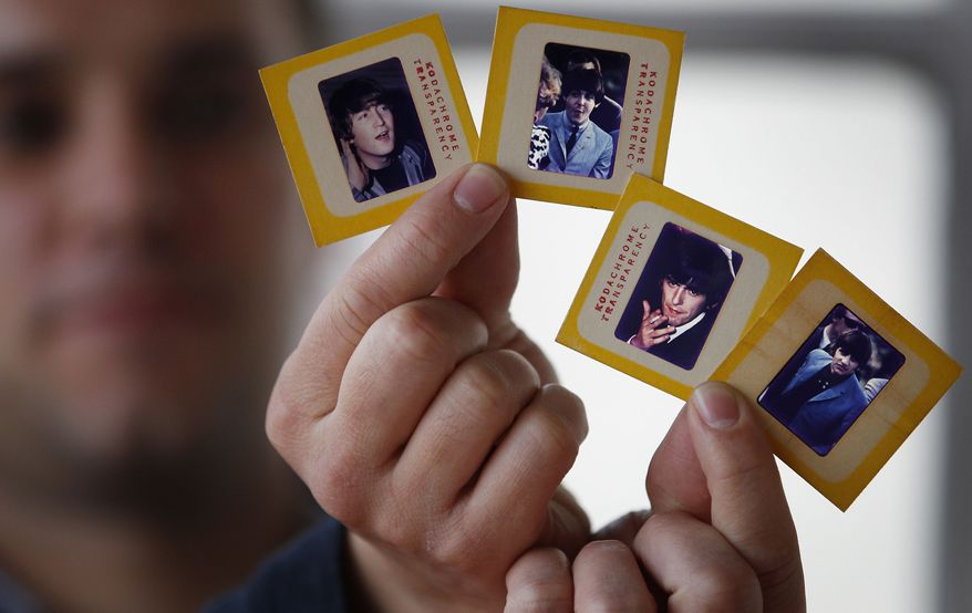 Auctioneer Paul Fairweather holds four color transparencies of the Beatles taken during their first tour of the United States in 1964. The rare images, taken by Dr. Robert Beck, are to be sold along with the copyright at Omega Auctions in Stockport, England, in a special Beatles memorabilia auction in March. The unpublished collection of 65 slides contains many stage shots. (AP Photo/PA, Dave Thompson)