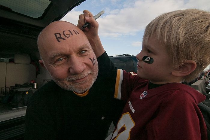 Walter Novak, 68, from Eastern Shores, Md. has his grandson Dominic Jr., 9, write RGIII on his forehead with sharpie in preparation for the Redskins NFC wild card game against the Seattle Seahawks, outside of FedEx Field in Landover Md., on Sunday, January 6, 2013. Walter became a Redskins fan when he was 6 years old at Griffith Stadium and has been passing down his fanhood to his son and now his grandson. (Craig Bisacre/The Washington Times)