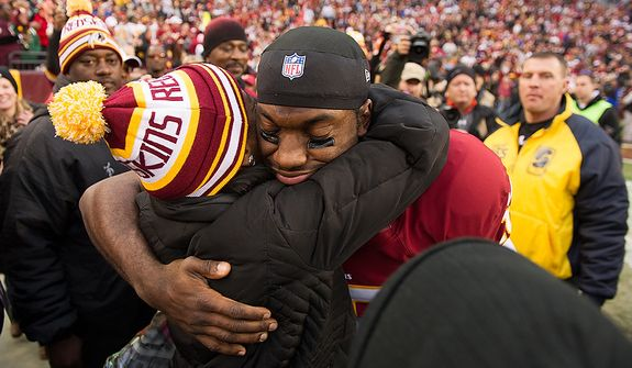 Washington Redskins quarterback Robert Griffin III (10) hugs friends and family on the sideline before the Washington Redskins play the Seattle Seahawks during the NFC wild card game at FedEx Field, Landover, Md., Sunday, January 6, 2013. (Andrew Harnik/The Washington Times)