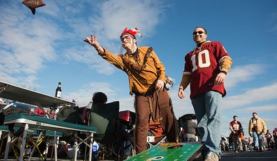 Redskins fans Ryan and Andrew Burtnick of Crofton, Md., play corn hole in the parking lot before the Washington Redskins play the Seattle Seahawks on wildcard weekend in NFL playoff football at FedEx Field, Landover, Md., Sunday, January 6, 2013. (Andrew Harnik/The Washington Times)