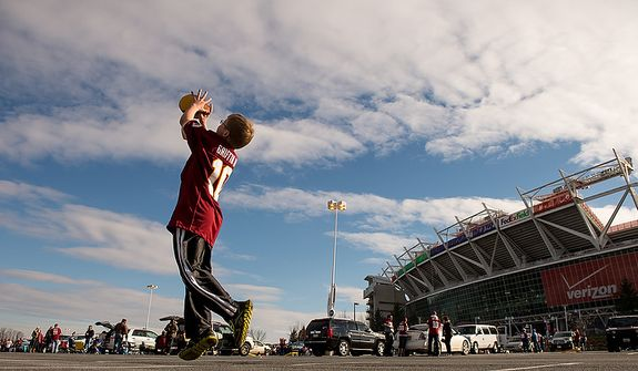 Jackson Clarke, 11, of Sterling, Va., tosses a football in the parking lot before the Washington Redskins play the Seattle Seahawks on wildcard weekend in NFL playoff football at FedEx Field, Landover, Md., Sunday, January 6, 2013. (Andrew Harnik/The Washington Times)