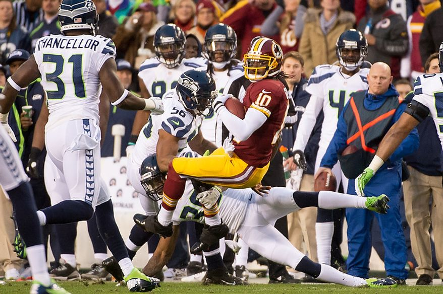 Washington Redskins quarterback Robert Griffin III (10) scrambles for a 3 yard gain in the first quarter as the Washington Redskins play the Seattle Seahawks during the NFC wild card game at FedEx Field, Landover, Md., Sunday, January 6, 2013. (Andrew Harnik/The Washington Times)
